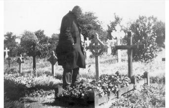 Photo of Arthur Conan Doyle standing by Innes Conan Doyle's grave (no date)