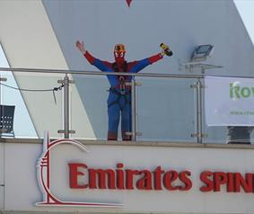 A man in a spider-man costume about to drop from the Spinnaker Tower