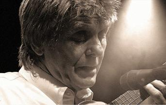 Close up image on Joe Brown playing an instrument and singing