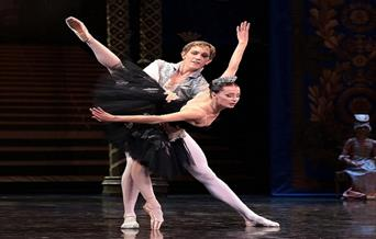 An image from the ballet, Swan Lake, showing a guy holding the princess