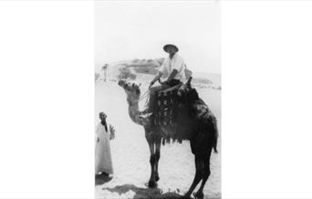 Photograph of Dennis riding a camel